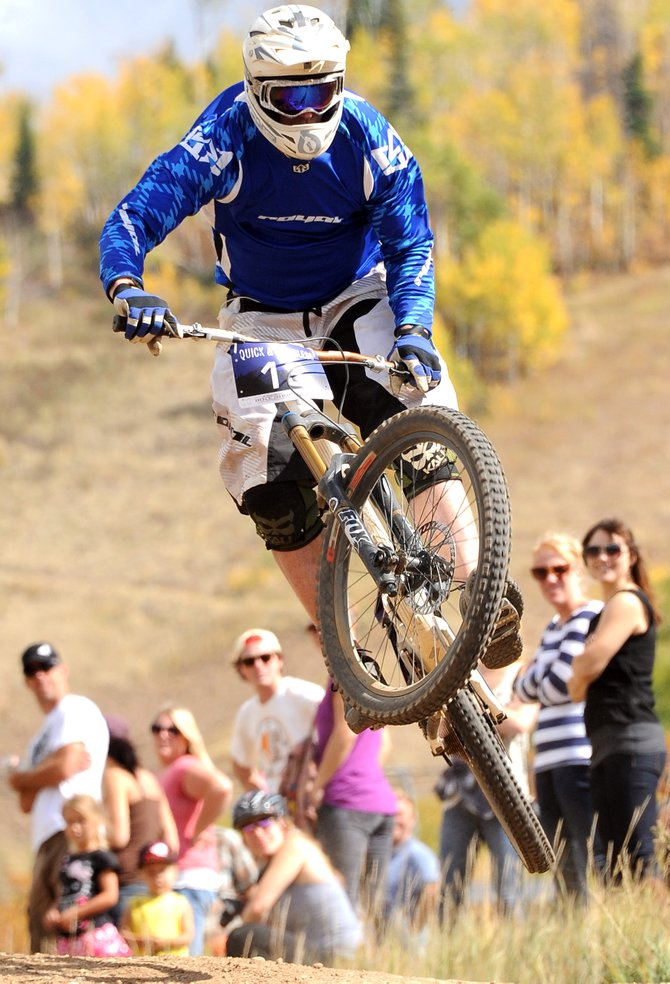 Adam Smith flies over a jump as the crowd cheers at the Quick and Chainless Downhill Mountain Bike Race at Steamboat Ski Area. The event drew a large crowd of riders eager to compete on the ski area's downhill trails.