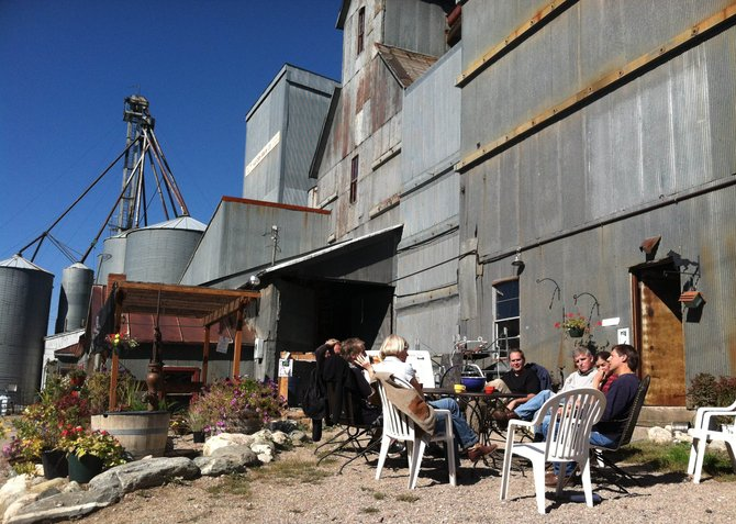Tammie and Patrick Delaney, owners of the Hayden Granary, sit in front of the building Saturday morning with a group of those interested in its future.