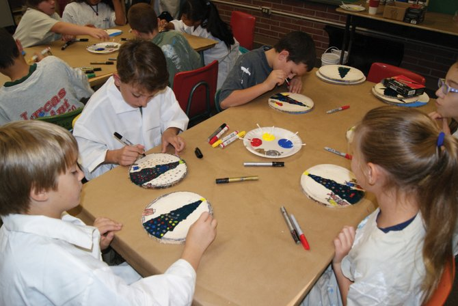 "Fourth graders at Sunset Elementary paint ornaments for the Capitol Christmas Tree during art class. The tree comes from Meeker this year, with the theme, ""Celebrating the Great Outdoors."""