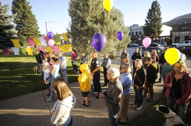 Supporters of the Advocates Building Peaceful Communities organization gather on the Routt County Courthouse lawn Thursday during a vigil to honor victims of domestic violence and sexual assault.
