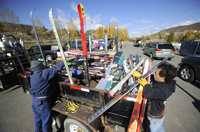 Javier Loya, left, and Danny Kramer stack old skis onto a trailer during the community recycling event Saturday at Howelsen Hill. There were 425 cars that came to the event packed with items to be reused or recycled. Items dropped off included 200 pairs of skis, 700 gallons of latex paint, 90 cubic yards of electronics and 200 gallons of plastic bags.