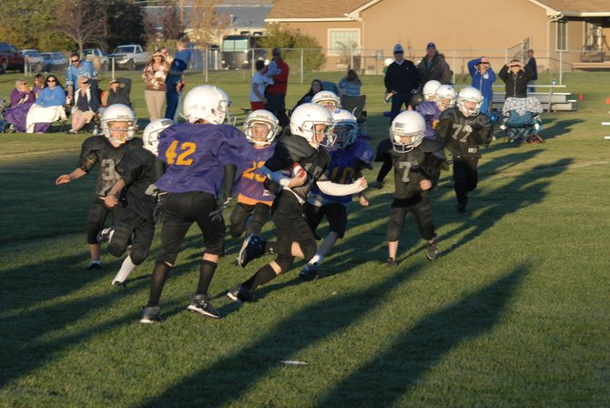 Joe Campagna (No. 10) carries the ball on a kick return Monday during the Raiders (black) and Vikings (purple) third/fourth grade Parks and Recreation game. Campagna would score on the return, but the Vikings would prevail, 34-32