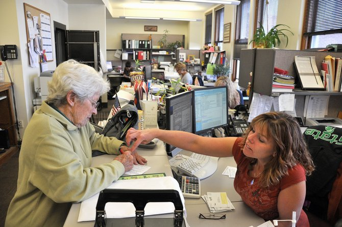 Steamboat Springs resident Katie Newton, left, changes her mailing address Monday with the help of Routt County Clerk Barbara Houston. Voters have until the end of the day Tuesday to register to vote.