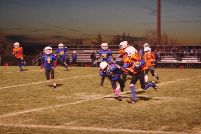 A runner from the Broncos, sponsored by Anson Excavating, tries to get around the corner Tuesday during the team's Doak Walker fifth and sixth grade league Super Bowl vs. the Chargers from Cook Chevrolet. The Broncos would win in a thriller, 32-28.