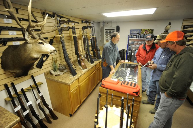 Elk River Guns owner Ken Constantine helps out-of-state hunters, from right, Shawn Levesque, Jim Perry and Roger Christiansen on Friday at the store.