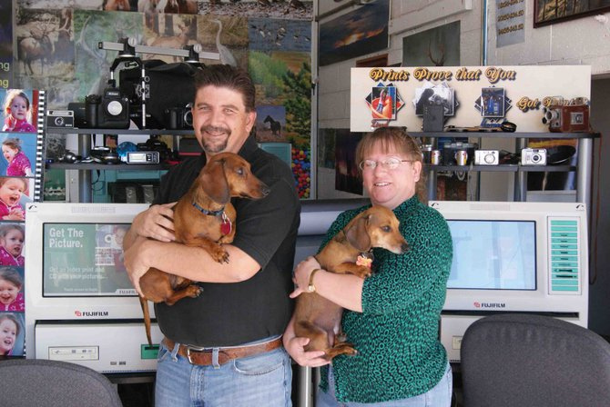 Robert Libbee and wife, Tina Libbee, owners of Quality Plus One Hour Photo in Craig, stand inside their business with dachshunds Snickers and Candy, mascots for the business. Robert said that despite the business's name and the fact it still processes film, it also offers a wide range of digital photo options.