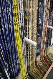 A rack of hockey sticks displayed in Samuelson True Value Hardware, located at 456 Breeze St.