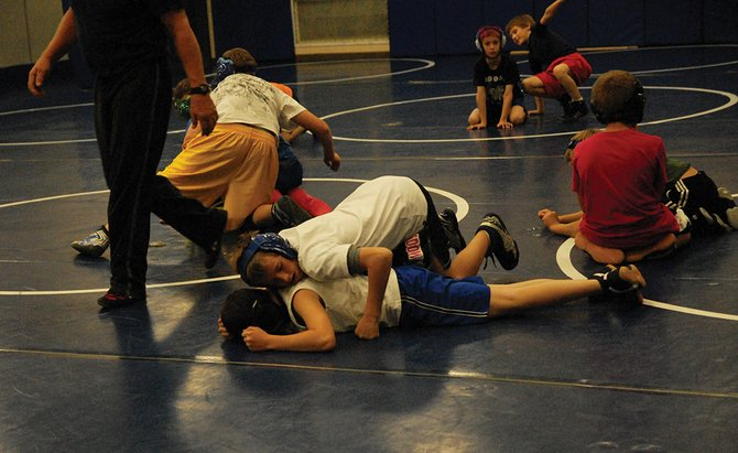 Devlin Mosman works on a takedown move at Bad Dogs wrestling practice Thursday in the Moffat County High School wrestling room. The Bad Dogs Youth Wrestling team started practice last week, and wrestlers will have their first tournaments this weekend.