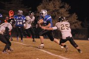 Bubba Ivers carries the ball and splits two Battle Mountain defenders during the first half of Friday's game at the Bulldog Proving Grounds. Moffat County won, 48-14.