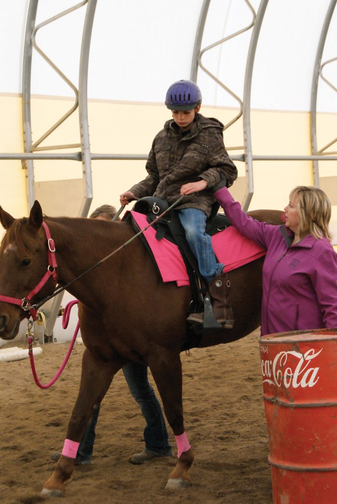 Connie Sue Ellis, right, helps direct Austin Flanders during a therapeutic riding session at her riding center. Austin is participating in a new pilot program, Freedom Hooves.