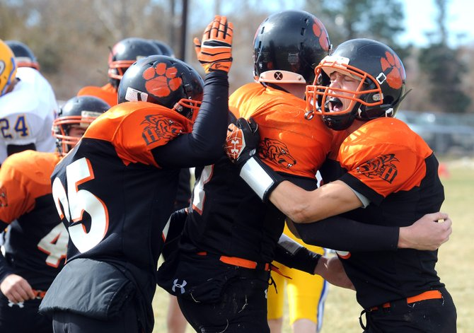 Hayden's Dan Engle, left, celebrates with Mark Doolin, center, after a touchdown in Saturday's win against Simla.