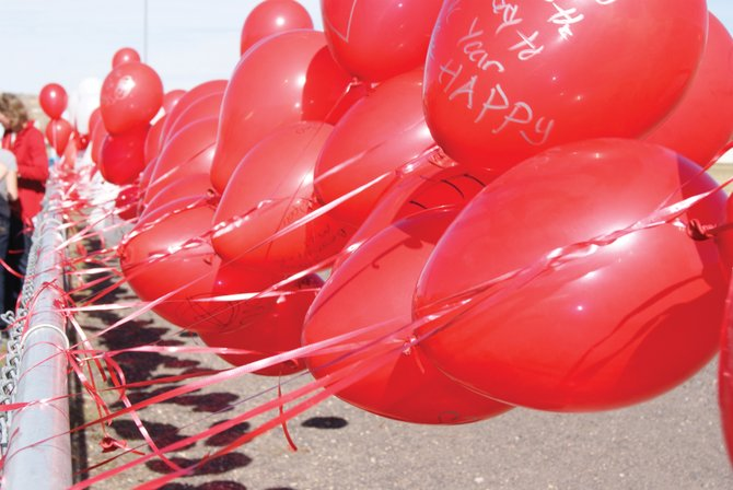 Red and white balloons line the fence at Craig Middle School Tuesday afternoon. Part of Red Ribbon Week,  a drug and alcohol prevention campaign, students wrote drug free messages on the balloons and then released them into the air.