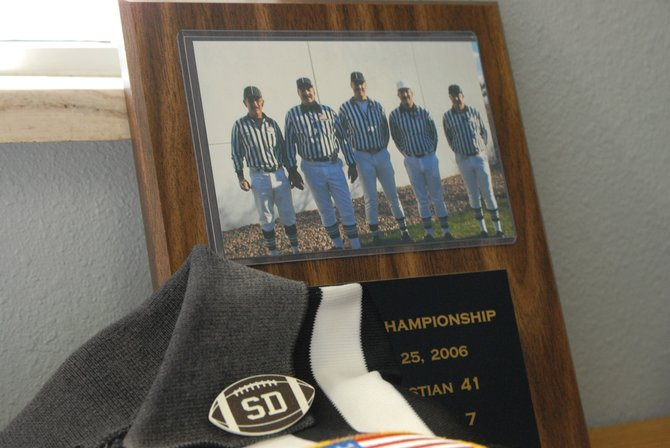 "Craig native Steve Deyo, who died in January, will be inducted to the Colorado Football Officials Association Hall of Fame next month. This ""SD"" pin was worn by his fellow officials and the coaching staffs of local teams this season in memory of Deyo. It sits in front of a plaque with (from left) Joe Zuniga, Deyo, Burl McMillen, Elvis Iacovetto and Pete Kohler, the referee crew for the 2006 Colorado 2A state championship game."
