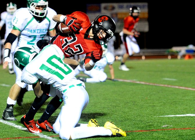 Steamboat's Mitch McCannon is dragged down by a pair of Delta defenders Friday night. Steamboat lost, 35-0.
