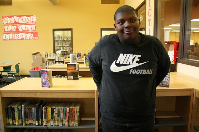 Devnnte Johnson, an eighth grade student at Craig Middle School, leans against a book shelf in the CMS media center.