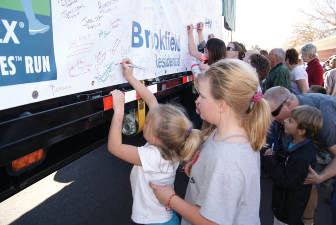 Craig elementary students take turns signing the tarp protecting the Capitol Christmas Tree Tuesday afternoon at the Moffat County Fair Grounds. The tree stopped in Craig on it's way from Meeker — near where it was harvested — to Washington, D.C.