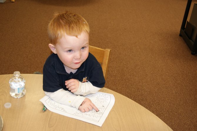 Logan Anthony, 3, works on a picture he's coloring after listening to the story-time launch event of Dolly Parton's Imagination Library at the Craig branch of Moffat County Libraries. The program provides free books to kids from birth to age 5.