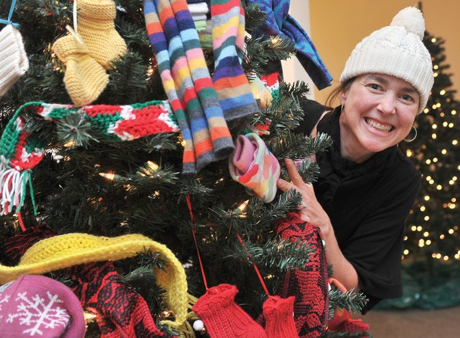 "Candice Bannister, executive director of the Tread of Pioneers Museum, peeks out from behind the ""Giving Tree,"" which was decorated by LIFT-UP of Routt County for this year's Festival of Trees. The annual Tread of Pioneers Museum fundraiser is scheduled to run Saturday through Nov. 19 this year, and is open and free to the public from 11 a.m. to 5 p.m. every day."