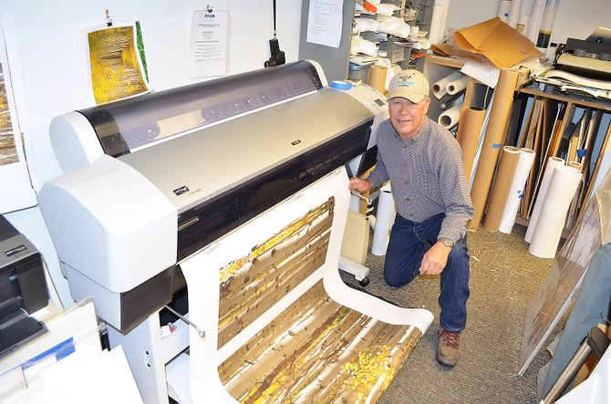 Photographer Don Tudor pulls an image of fall aspen trees from the printer Tuesday morning in the back room at the Sleeping Giant Gallery. The gallery at 601 Lincoln Ave. is closing at the end of November after nine years in downtown Steamboat Springs.