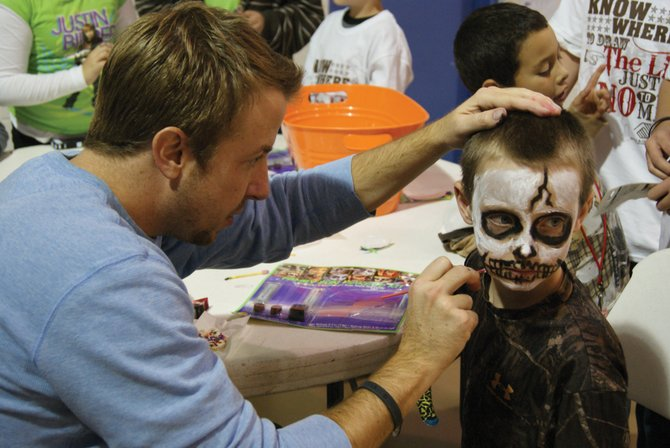 Jonathan Judge, program manager for the Colorado Meth Project, paints the face of David White, 10, at the Boys and Girls Club Thursday night.