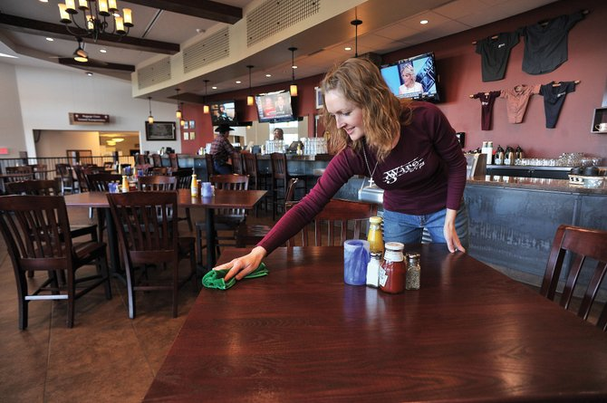 Employee Karleen Booco cleans off tables at Three Wire Bar & Grill at Yampa Valley Regional Airport on Thursday afternoon. The restaurant, which is run by the county, was created during the last phase of improvements and  has been operating at a loss during its first year.