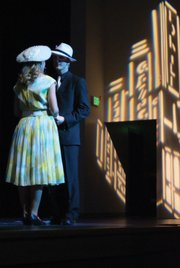 "Sarah Brown, left, played by Caitlin Harjes embraces Sky Masterson, played by Derek Maiolo during the song, ""I've never been in love before,"" at MCHS's Friday night performance of ""Guys and Dolls."""