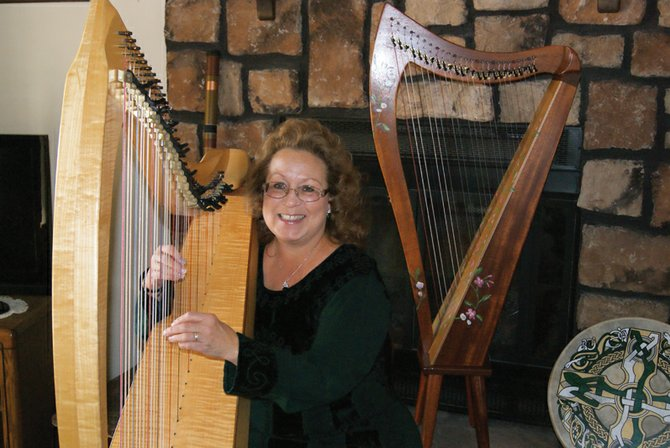 Craig resident Charleah Firestone sits with her harps in her home. She will be giving performances at 2 p.m. December 1 and 6 p.m. December 3, at the Moffat County Public Library in Craig.