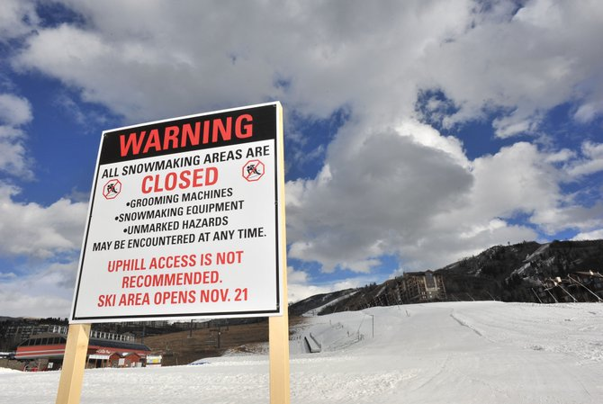 Signs are set up at Steamboat Ski Area warning skiers about snowmaking operations and cautioning them about potential dangers of making the trek up the mountain for a few early season turns. Citing an effort to promote skier safety, ski area officials are asking those uphill upstarts to read through a list of dangers and don a free reflective armband made available by the ski area.