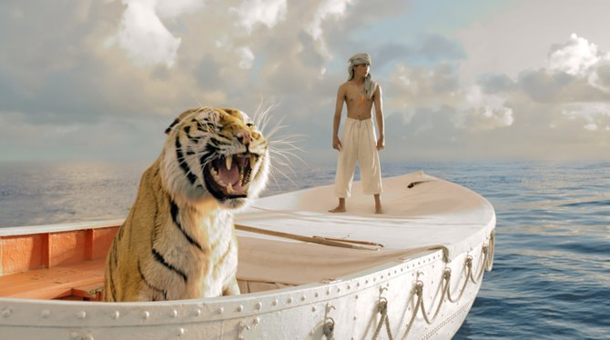 Pi Patel (Suraj Sharma) and his feline traveling companion Richard Parker survey the emptiness of the ocean in Life of Pi. The movie is about an Indian teenager who survives a shipwreck and must live for weeks alone on a lifeboat with an adult Bengal tiger.