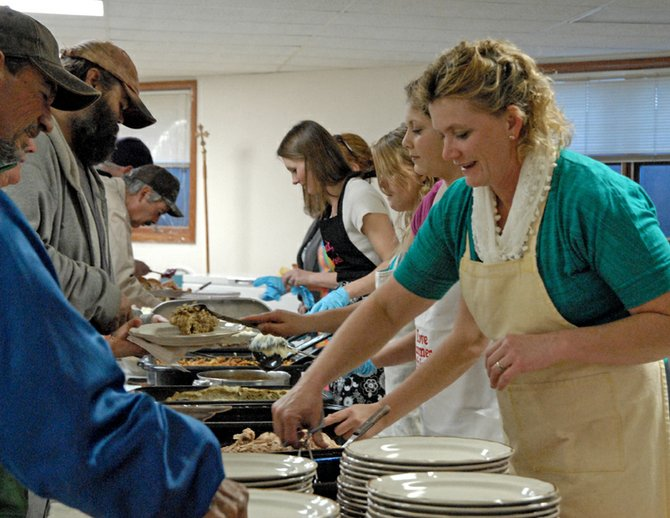Volunteer Jenny Knez serves patrons Thursday during the third annual St. Michael's Catholic Church Thanksgiving dinner. About 150 to 200 residents took part in the holiday feast.