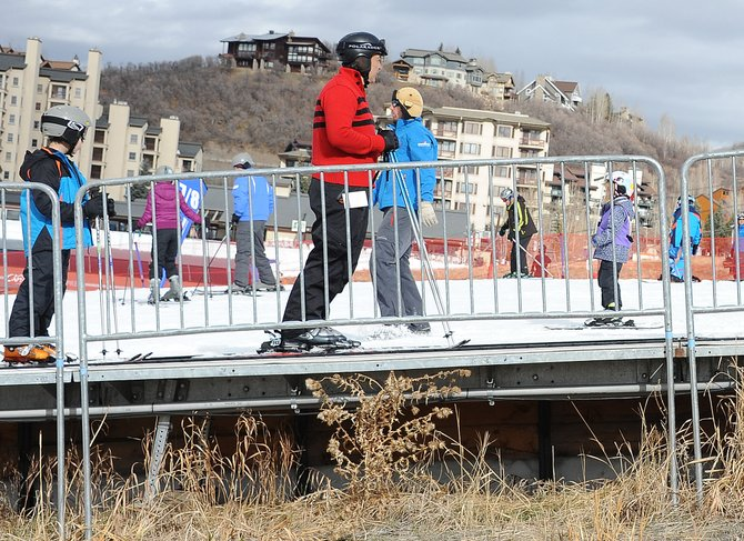 "Beginner skiers ride a magic carpet at Steamboat Ski Area on Thursday, the first day season passes were accepted. With as much mud around as snow, it definitely was a ""make the most of it"" kind of day and plenty did."