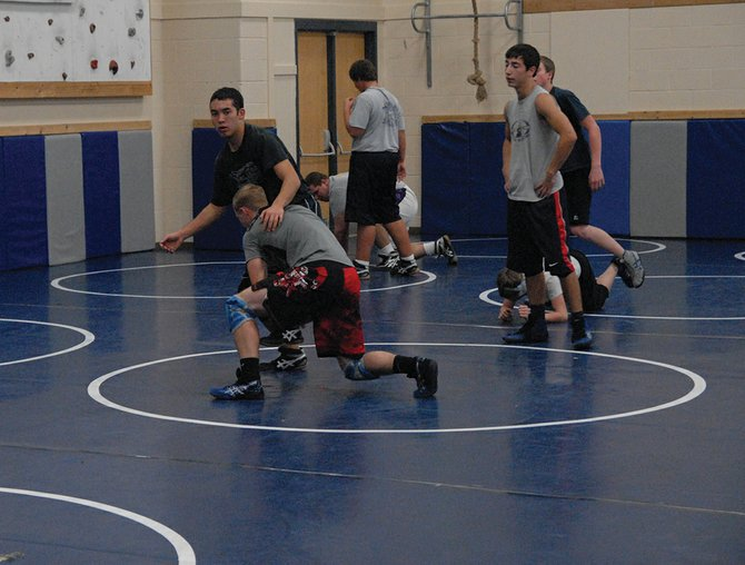 Garrett Stewart (in red shorts) picks up teammate Jacob Teeter during a drill at wrestling practice last week. Stewart, in his senior year at Moffat County High School, is the wrestling team's returning state qualifier.