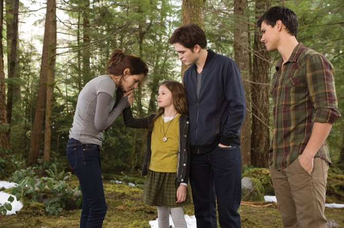 New vampire Bella (Kristen Stewart) communicates with her daughter, Renesmee (Mackenzie Foy), alongside husband, Edward (Robert Pattinson), and friend Jacob Black (Taylor Lautner) in The Twilight Saga: Breaking Dawn  Part 2. 