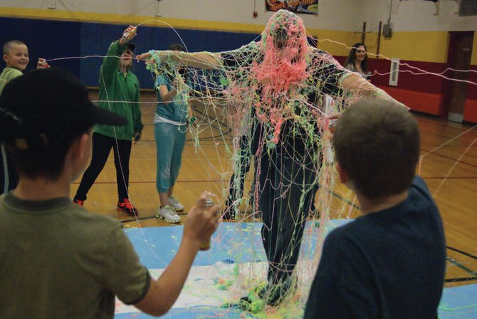 Sandrock Elementary School fourth and fifth graders spray principal Kamisha Siminoe with silly string Friday afternoon in the gym. Siminoe allowed any student who met her challenge of selling 20 items during a school fundraiser to spray her.