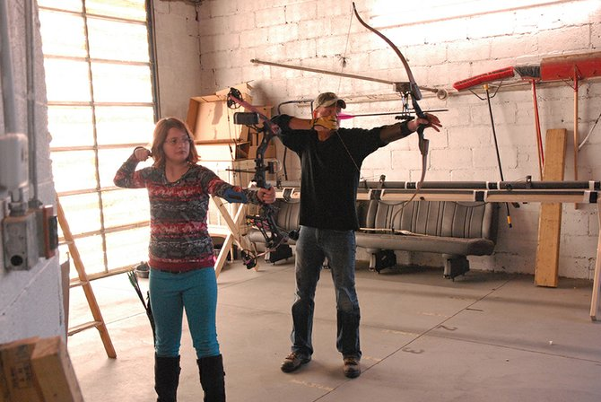 Winter Rogers (left), 10, and her father Bob take aim and shoot from the 20-yard line on the archery lanes at InsideOut Sports, 561 Russell St., during the business' grand opening Saturday. InsideOut offers baseball and softball batting cages as well as the archery lanes indoors.
