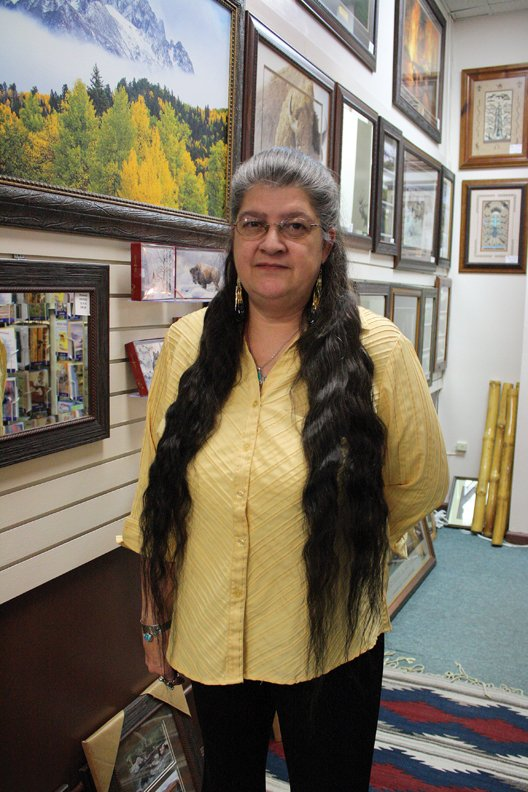 Christine Muzik, owner of Spirit Pass in Centennial Mall, stands in front of some of the photographs and other works of art for sale in her store. Muzik's business began 10 years ago this month with a small rented space in which she sold some of her handmade crafts.