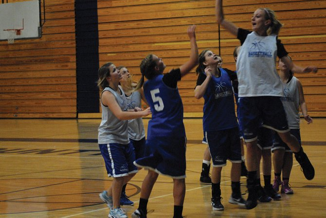 Bailey Hellander (right, in white) goes up to block teammate Jazmine Swindler's shot during a practice in the Moffat County High School gym. All three girls teams from MCHS played three games over the weekend in Vernal, Utah.
