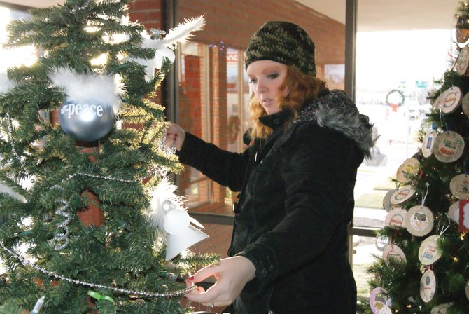 Laurie Cotten, a junior at Moffat County High School and part of the Moffat County Youth United Way and Key Club, decorates the groups' combined Christmas Tree at the Moffat County Courthouse Tuesday afternoon for the Festival of Trees. The trees will be on display beginning Thursday until December 26. There will be special community events from 5 -7 p.m. every Thursday throughout the month of December.