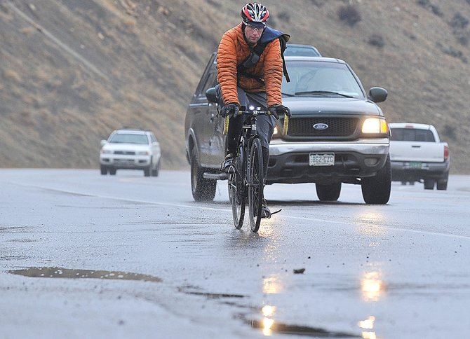 Cyclist Matt Pronovost rides to work in wet conditions Thursday morning. Bike shops across Steamboat Springs have been hard at work lately preparing bicycles for winter.