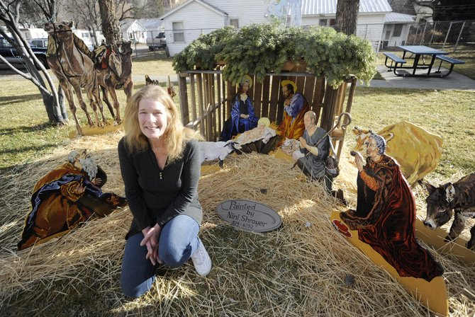 Craig artist Nini Shroyer sits Dec. 1 in front of the nativity scene she was commissioned to create for Hayden.