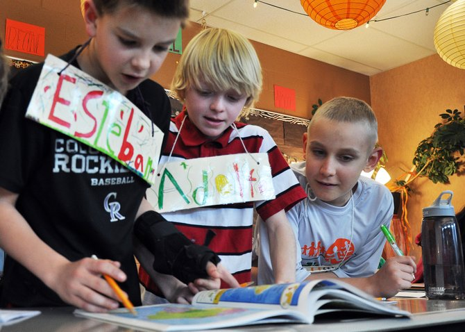Soda Creek Elementary School fifth-grader Izaac Kinnison, right, works with classmates Liam Baxter, center, and Ethan Hansen during a Spanish class Monday. Kinnison is back in school after successfully fighting a malignant brain tumor.