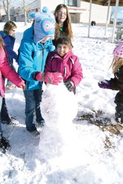 Ridgeview fourth grader McKinley Winkler, left, helps third grader Sofia Lopez build a snowman Tuesday during an afternoon recess. Students were excited to play in the snow after the huge dump the day before.