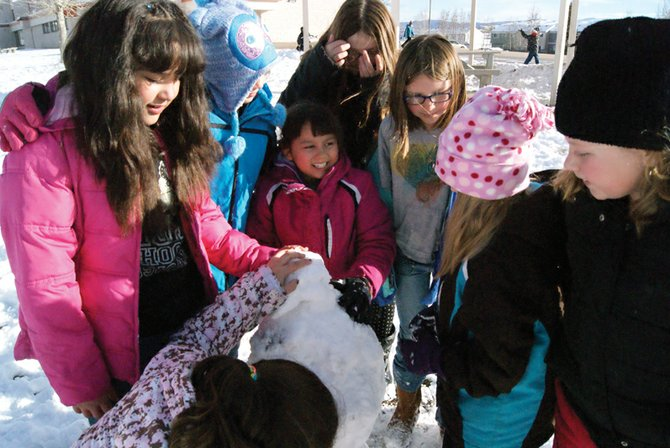 From left, Ridgeview fourth-grader Maria Balbuena, Mckinley Winkler, fourth grade, Sofia Lopez, third grade, Gwenevere Doizaki, fourth grade, Tressa Otis, fourth grade, Nadeia Koran, third grade, and Merinda Ross, third grade, play outside Tuesday afternoon and help build a snowman during recess.