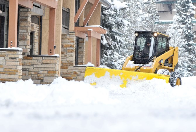 Clint Henry, of Prestige Property Detailing, clears the parking lot at the Phoenix Condominiums in Steamboat Springs.