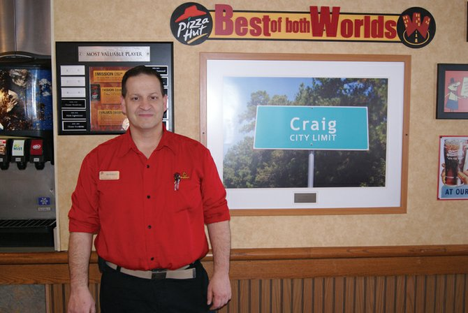 The Craig Pizza Hut's new general manager, Ken Prescott, stands inside the restaurant. Though only in his current post as manager for less than two months, customers already have noticed his excellent customer service.