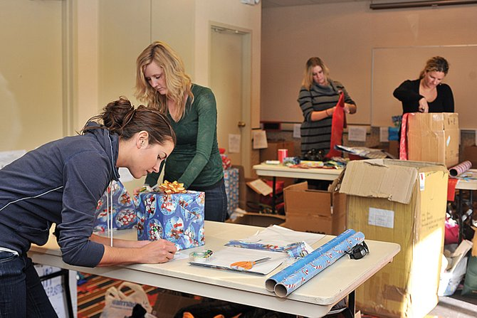 Stephany Swinford, from left, wraps presents along with Maren McCutchen, Sarah Leonard and Sara Ferris at Sheraton Steamboat Resort on Thursday afternoon. Volunteers from the Young Professionals Network and Steamboat Springs Chamber Resort Association have been busy wrapping hundreds of presents as part of Routt County United Way's Holiday Wishes program.