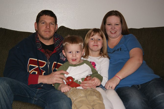 John Simonette, left, Jase Simonette, 2, Madison Simonette, 5 and Ashley Simonette sit together on their couch at home. Big sister Madison and Jace have both worked with speech therapist Mona Entwhistle from Horizons early intervention program.