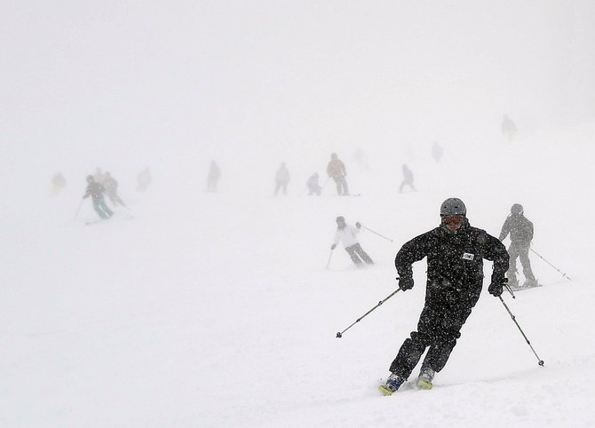 Heavy snow and wind kept visibility down on Buddy's Run, but it didn't keep away skiers, who emerge from the cloud at Steamboat Ski Area on Sunday.