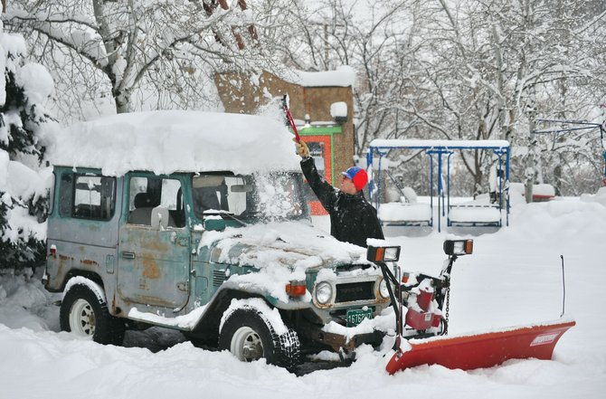 Brock Webster cleans the snow off of his 1977 Toyota Land Cruiser on Monday morning. Steamboat residents were greeted by another storm and more snow Monday, and the National Weather Service in Grand Junction is calling for 100 percent chance of snow through Tuesday night.