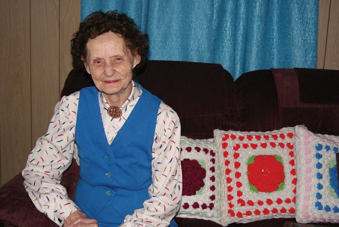 Craig resident Stella Hall sits in her home next to pillows she crocheted.